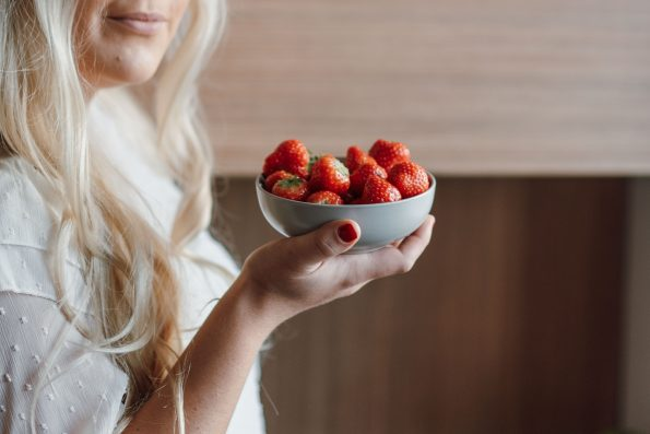 woman holding bowl of strawberries
