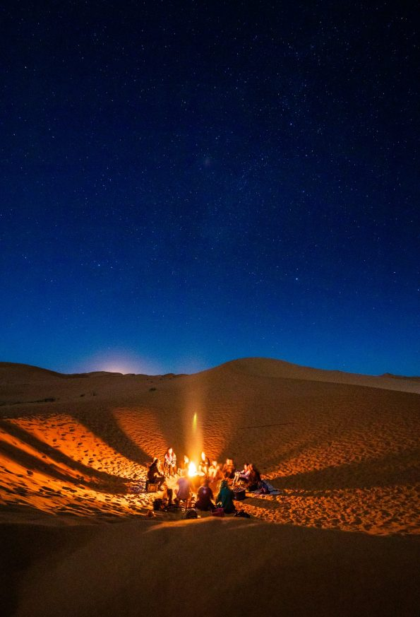 People sitting around a bonfire in the desert during nighttime