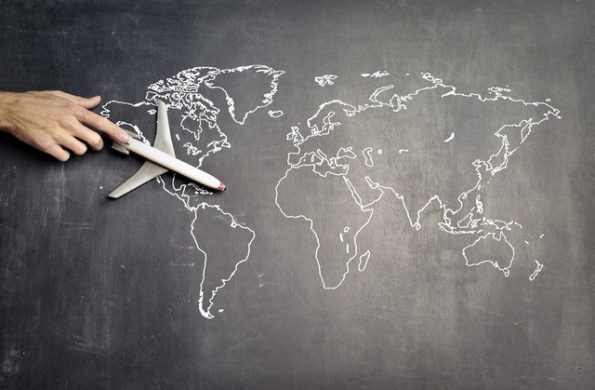 Miniature airplane and hand of a person over the drawn world map