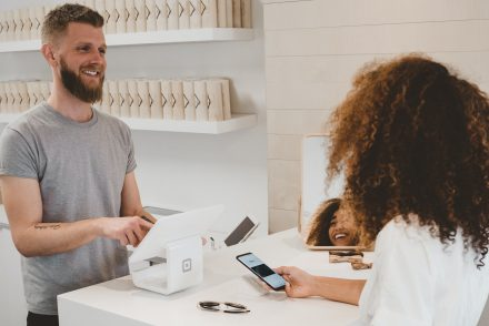 Sore owner and customer smiling at the pay counter