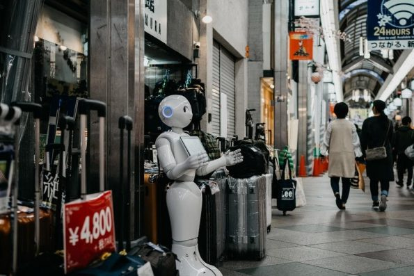 White AI robot standing near luggage bags