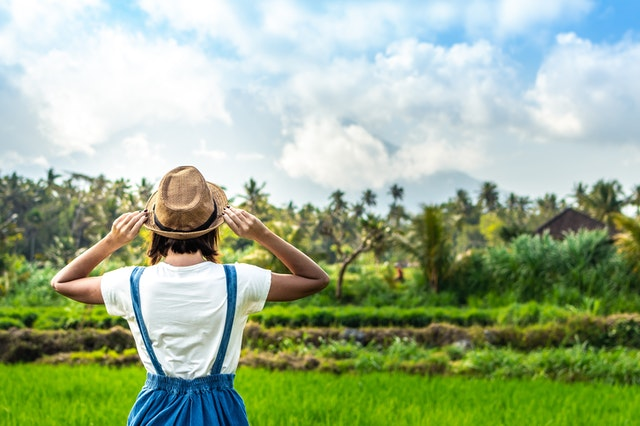 A woman with a hat standing in front of a green field