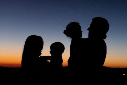 A silhouette of a family of four